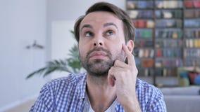 Homem ocasional pensativo da barba que pensa e que trabalha no portátil filme