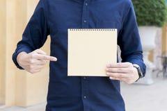 Homem ocasional que aponta o dedo no caderno vazio no dia ensolarado Imagem de Stock Royalty Free