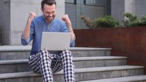 Homem ocasional que comemora a vitória no portátil que senta-se em escadas vídeos de arquivo