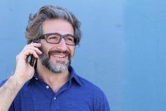 Homem ocasional que fala no telefone celular isolado no azul com espaço da cópia Fotografia de Stock