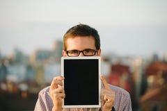 Homem ocasional que mostra a tabuleta digital a tela vazia Fotografia de Stock