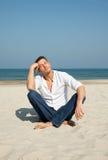Homem ocasional que senta-se na praia Fotografia de Stock Royalty Free