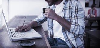 Homem ocasional que usa o café bebendo do portátil Foto de Stock Royalty Free