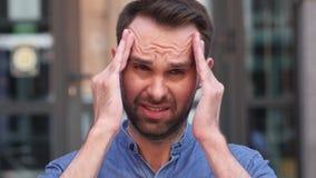 Homem ocasional tenso com a dor de cabeça que está fora da construção video estoque