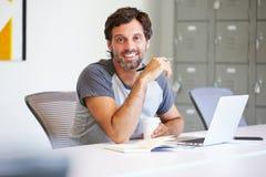 Homem ocasionalmente vestido que trabalha no estúdio do projeto fotos de stock