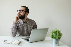 Homem ocupado com a barba nos vidros que pensa sobre o portátil e o smartpho Foto de Stock Royalty Free
