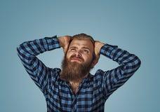 Homem olhando de sobrancelhas franzidas novo que cobre as orelhas com as mãos que olham acima fotos de stock royalty free