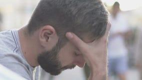 Homem oprimido que senta-se na rua, homem novo chocado pelas más notícias, lento-mo video estoque