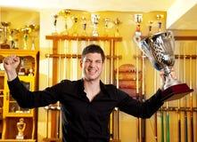 Homem orgulhoso feliz do vencedor com o copo grande da prata do troféu fotos de stock royalty free