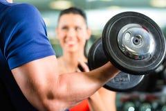 Instrutor pessoal no gym e no treinamento do dumbbell Fotografia de Stock Royalty Free