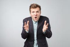 Homem ou empregado louco de negócio que gritam, sendo virado sobre a situação, resultado de seu caso, fundo branco isolado imagem de stock
