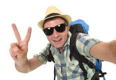 Homem ou estudante atrativo novo do mochileiro que toma a foto do selfie com telefone celular ou câmera foto de stock