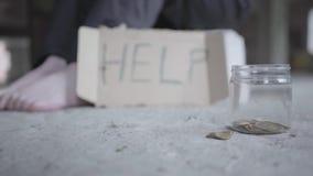 Homem ou mulher desabrigada que sentam-se em uma construção abandonada com uma ajuda do sinal da caixa e no frasco para o apoio d video estoque