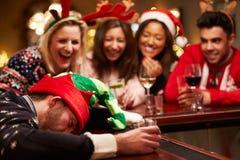 Homem passado para fora na barra durante bebidas do Natal com amigos Fotografia de Stock