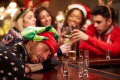 Homem passado para fora na barra durante bebidas do Natal com amigos Imagem de Stock