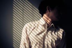 Homem pela janela com sombras das cortinas Imagem de Stock Royalty Free
