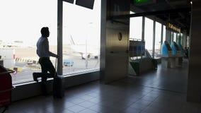 Homem pensativo com embarque de espera da mala de viagem e vista através da janela video estoque