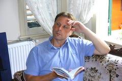 Homem pensativo considerável com um livro Imagem de Stock Royalty Free