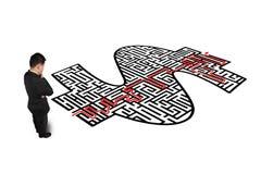 Homem pensativo na frente do labirinto da forma do dinheiro Fotos de Stock