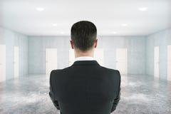 Homem pensativo na sala com portas Imagem de Stock Royalty Free