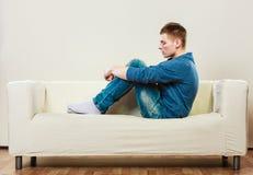 Homem pensativo novo que senta-se no sofá fotografia de stock royalty free
