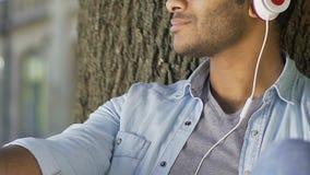 Homem pensativo que escuta a música nos fones de ouvido, pensando sobre o relacionamento video estoque