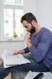 Homem pensativo que senta-se lendo um jornal Imagem de Stock