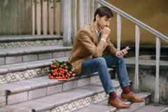 Homem pensativo que texting e que olha o telefone foto de stock