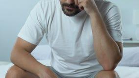 Homem pensativo triste que senta-se na cama, problema de saúde, dificuldades da vida, esforço video estoque