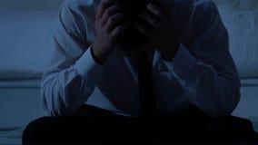 Homem pensativo triste que senta-se no esforço da cama, dos problemas de saúde e das dificuldades da vida filme