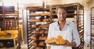 Homem pequeno feliz do proprietário empresarial que guarda croissant fotografia de stock