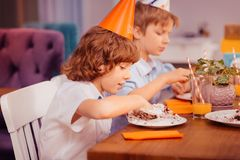 Homem pequeno satisfeito que come o bolo com mãos imagens de stock royalty free