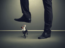 Homem pequeno sob o pé grande Fotos de Stock