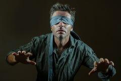 Homem perdido e confuso novo vendado os olhos com a gravata que joga o desafio viral perigoso da tendência do Internet com as cor fotos de stock royalty free