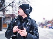 Homem perdido em cidade desconhecida usa GPS app no smartphone Foto de Stock Royalty Free