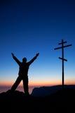 Homem perto da cruz de encontro ao céu no por do sol Fotografia de Stock