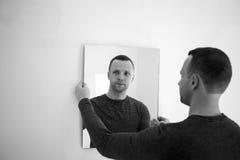 Homem perto da parede branca com espelho fotografia de stock