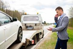 Homem perto de seu carro quebrado em uma borda da estrada Fotografia de Stock