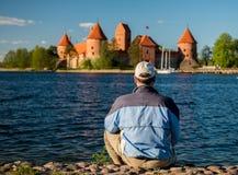 Homem perto do lago e do castelo Fotos de Stock Royalty Free