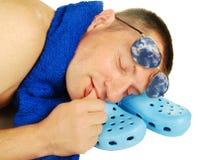 Homem, plimsolls, toalha e vidros adormecidos do antisun Fotografia de Stock