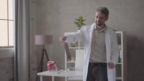 Homem positivo, bem sucedido e satisfeito considerável na dança branca da veste com raio X nas mãos na clínica moderna O doutor vídeos de arquivo
