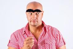 Homem positivo com sobrancelhas falsas, fundo branco com olhar surpreendido foto de stock
