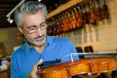 Homem positivo da Idade Média que compra violinos tradicionais na loja Fotografia de Stock Royalty Free