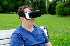 Homem positivo do tamanho que veste óculos de proteção da realidade virtual fora Imagens de Stock