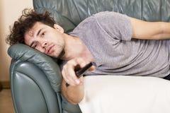 Homem preguiçoso com o telecontrole no sofá imagem de stock