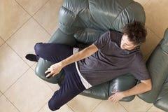 Homem preguiçoso com o telecontrole no sofá foto de stock royalty free