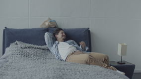 Homem preguiçoso que encontra-se na cama que sonha quando a esposa for ocupada video estoque