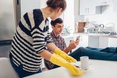 Homem preguiçoso que olha o telefone quando sua amiga irritada que limpa seus pratos na cozinha e que fala a ele Argumento da fam imagens de stock royalty free