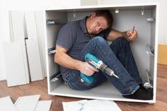 Homem prendido enquanto montando a mobília do bloco liso Imagem de Stock Royalty Free