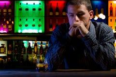 Homem preocupado que senta-se na barra com vidro do uísque. Dar fotos de stock royalty free